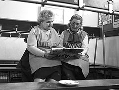 Two ladies reading a paper together. 